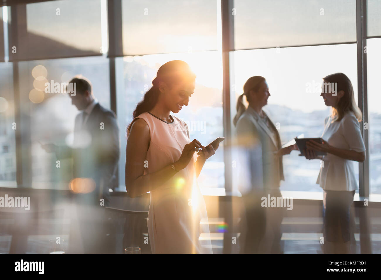 Businesswoman texting with cell phone in sunny conference room - Stock Image