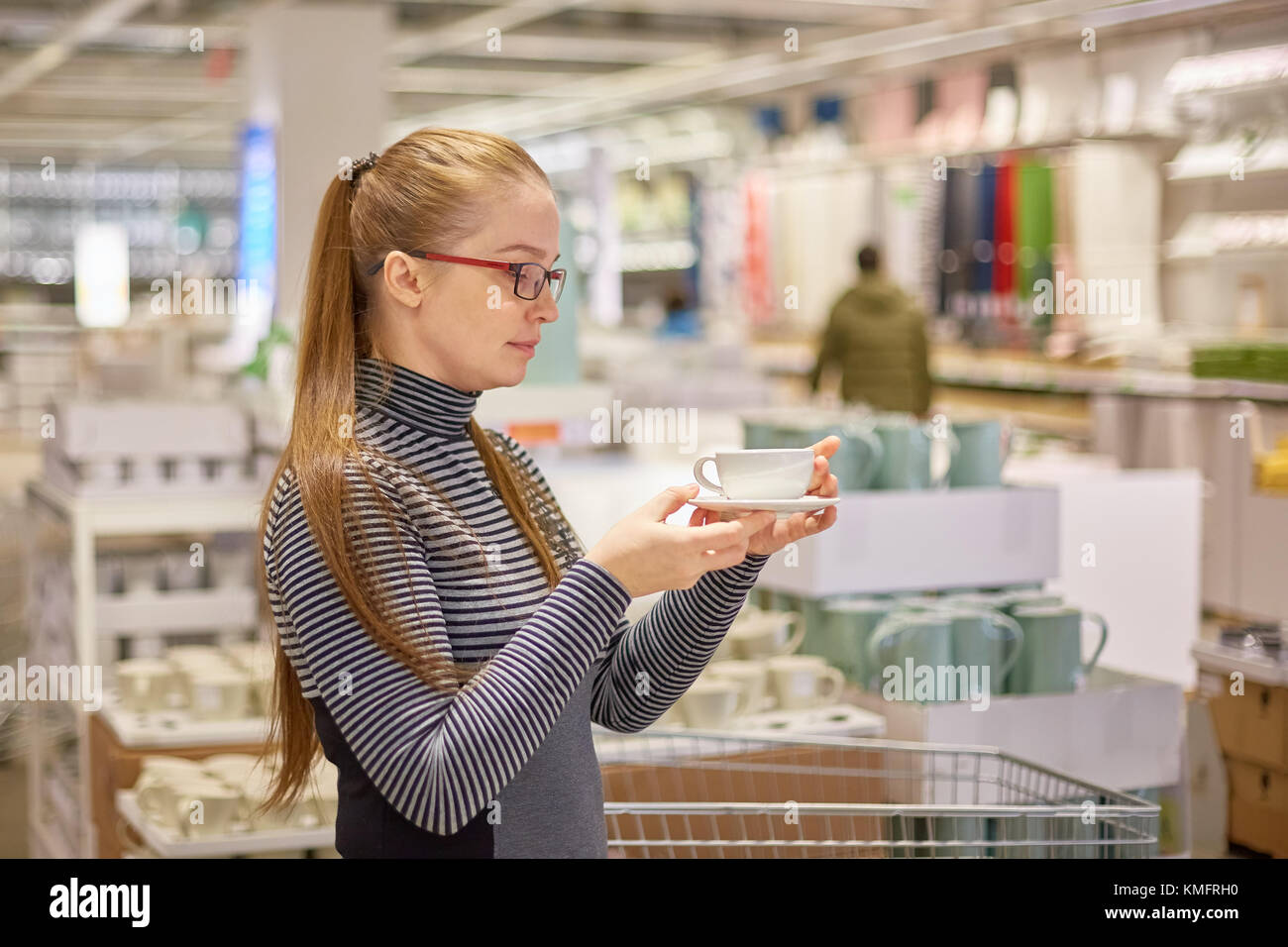 housewife chooses dishes in the store - Stock Image