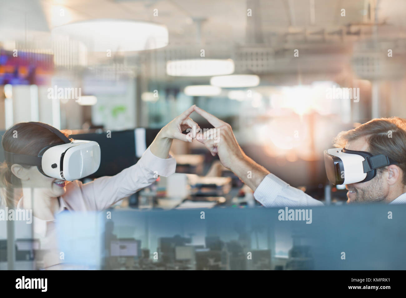 Computer programmers using virtual reality simulator glasses, touching fingers in office - Stock Image