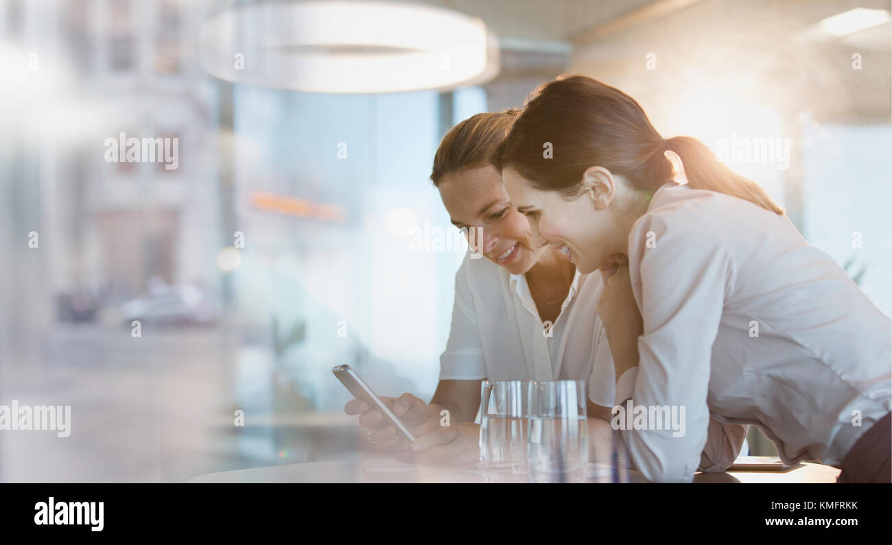 Businesswomen texting with cell phone in office - Stock Image