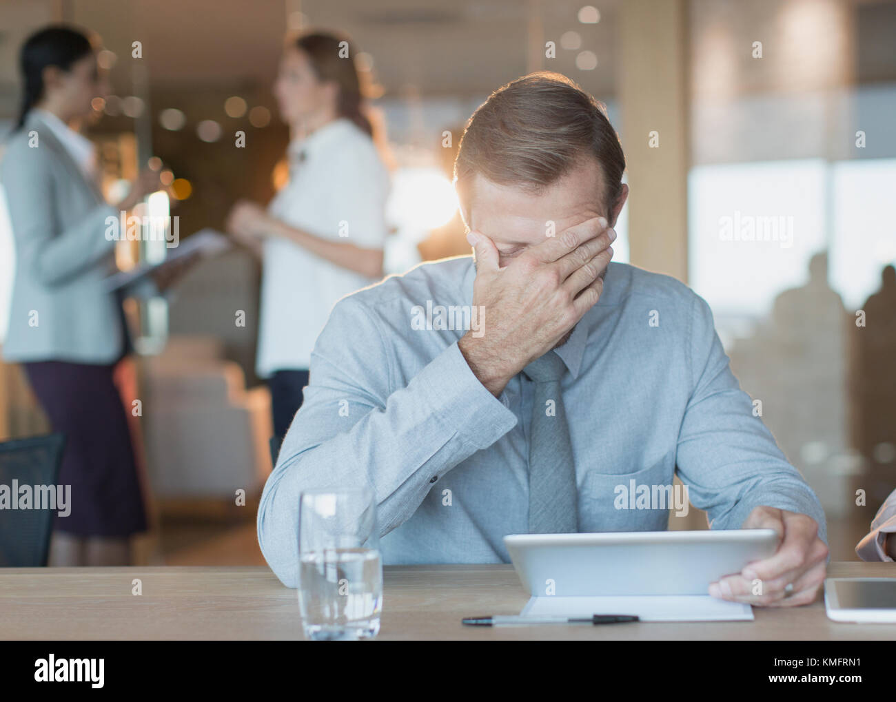 Tired, stressed businessman using digital tablet in conference room - Stock Image
