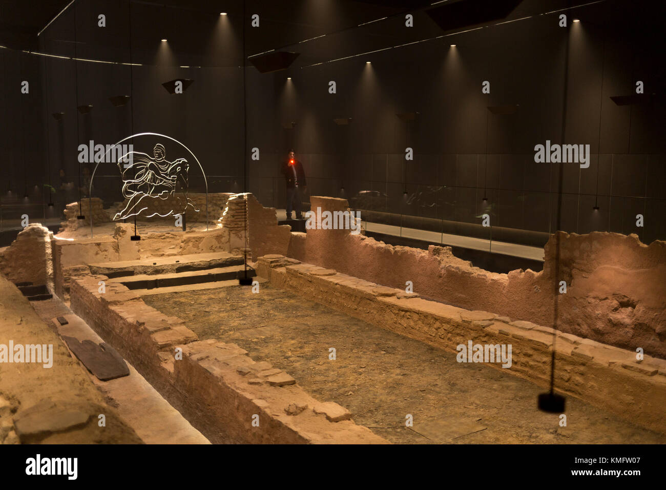 Atmospheric lighting helps display the reconstructed mid-3rd century Roman Mithraeum also known as the Temple of - Stock Image