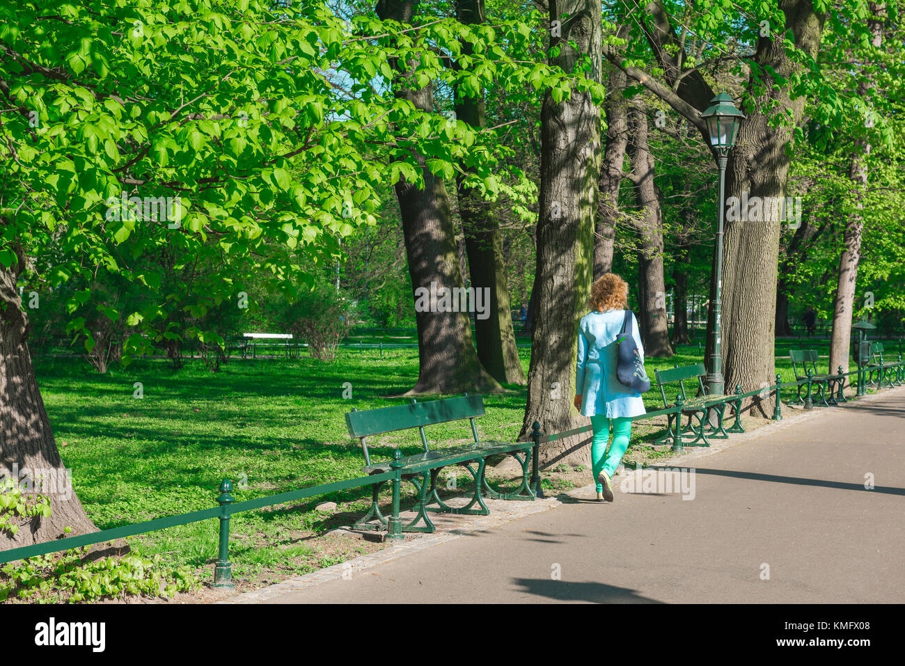 Woman walking alone, rear view of a woman wearing a blue raincoat walking through Planty Park in the center of Krakow, - Stock Image