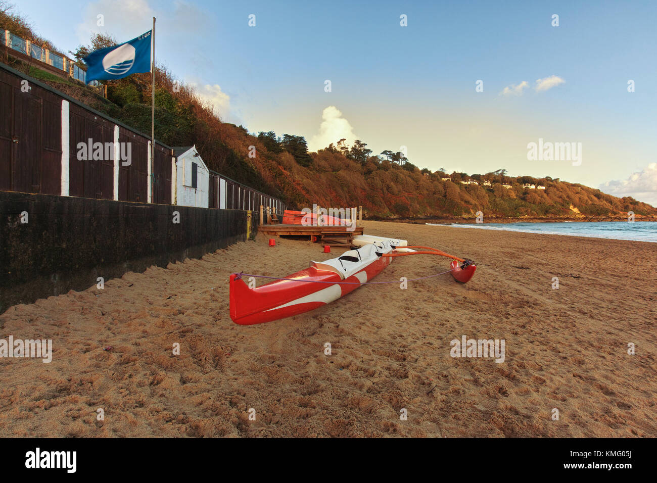 An outrigger boat lying on the beach at Carbis Bay near St Ives in Cornwall, South East England. - Stock Image