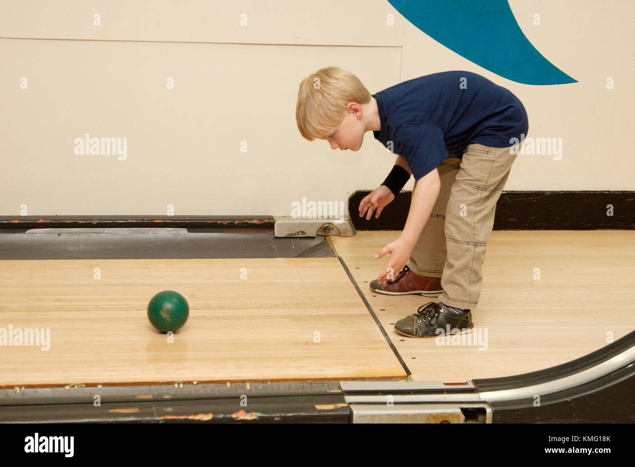 a young blonde boy bends over and launches bowling ball down an alley - Stock Image