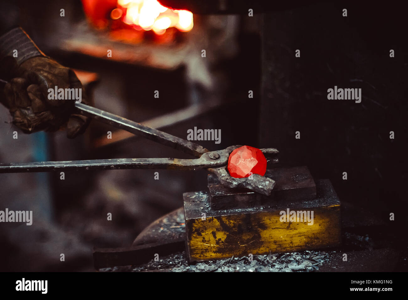 blacksmith working in the forge on auto hammer - Stock Image