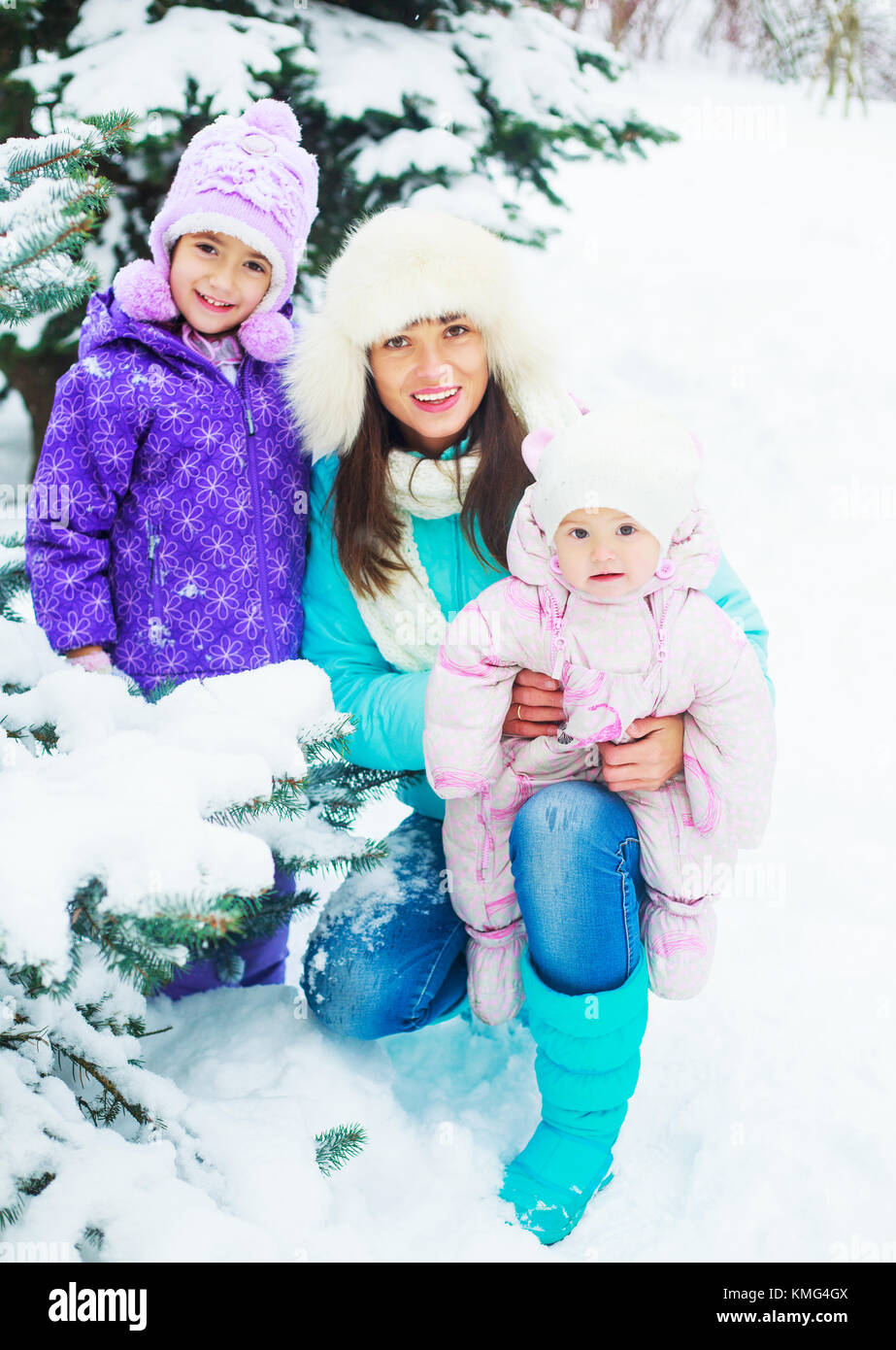happy young mother and two daughters outdoor in the winter park - Stock Image