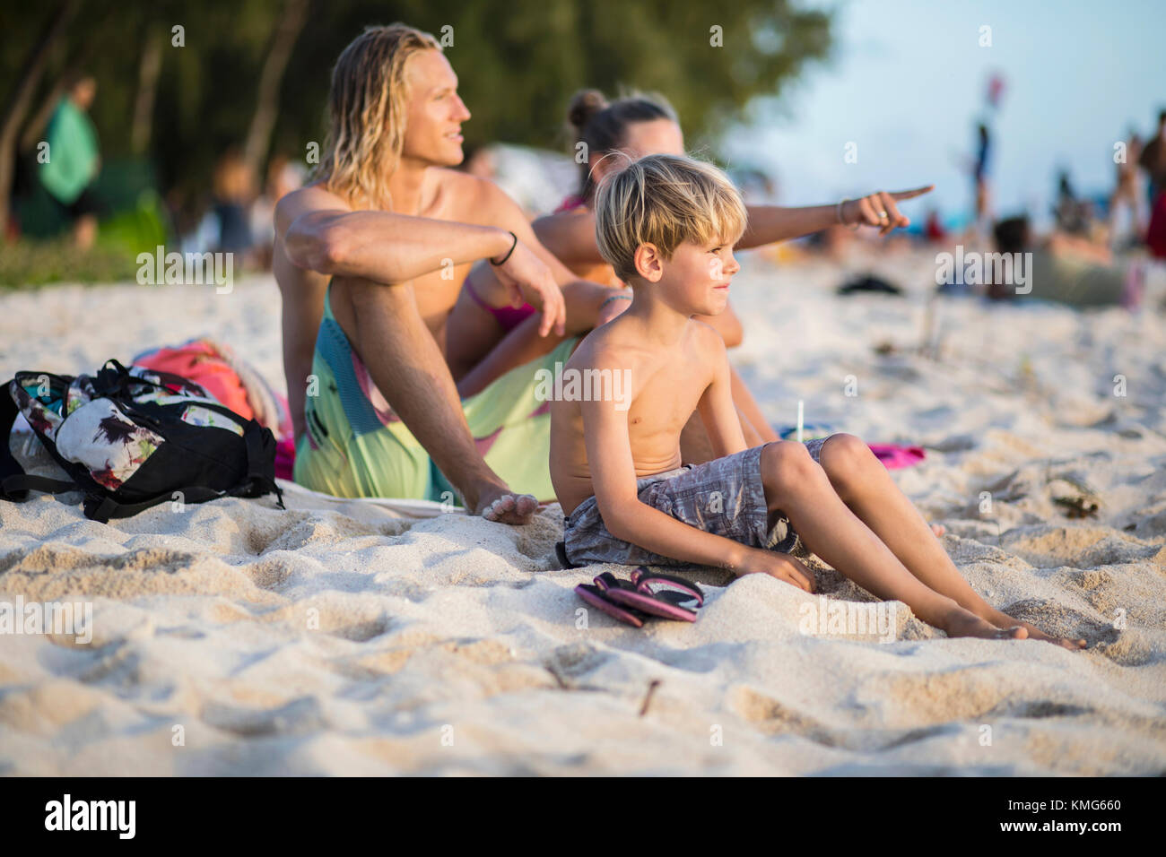 Family relaxing on sand at beach - Stock Image