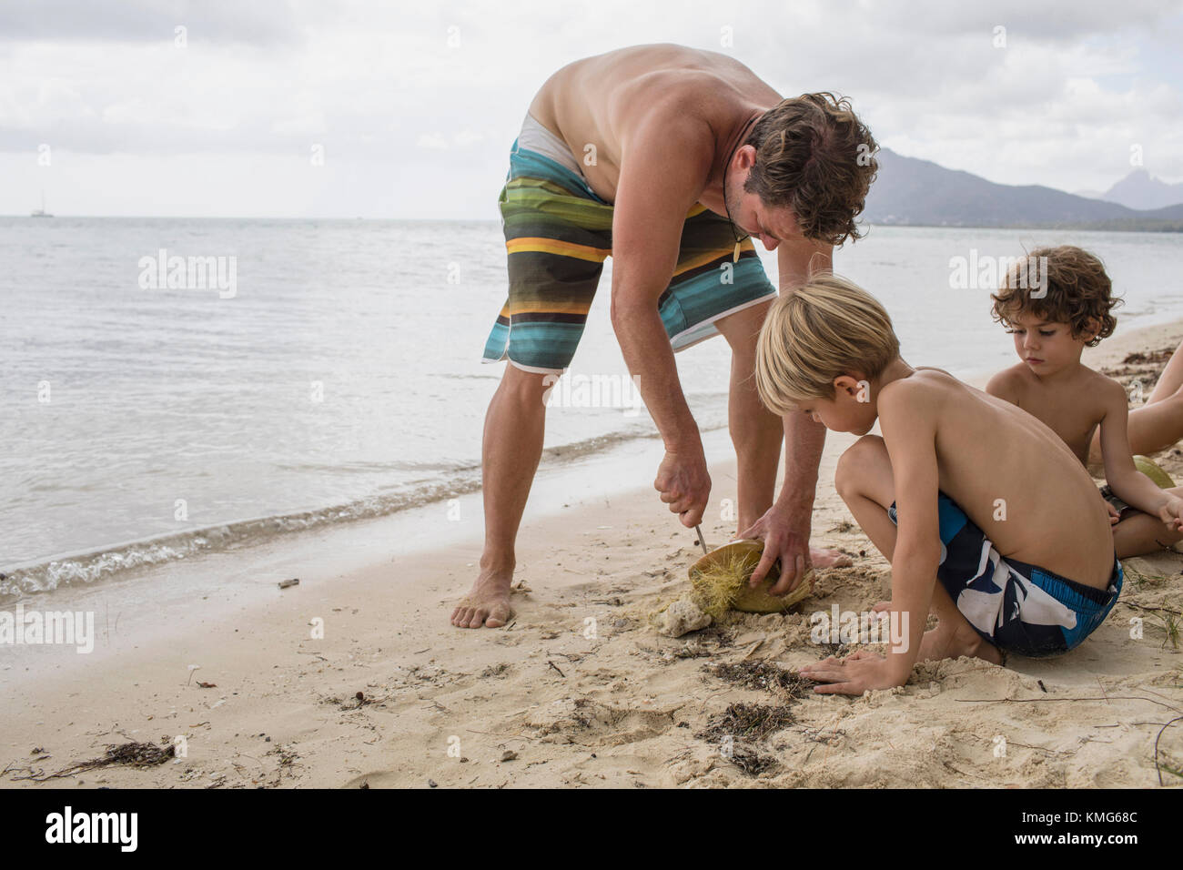 Children watching father opening coconut at beach - Stock Image