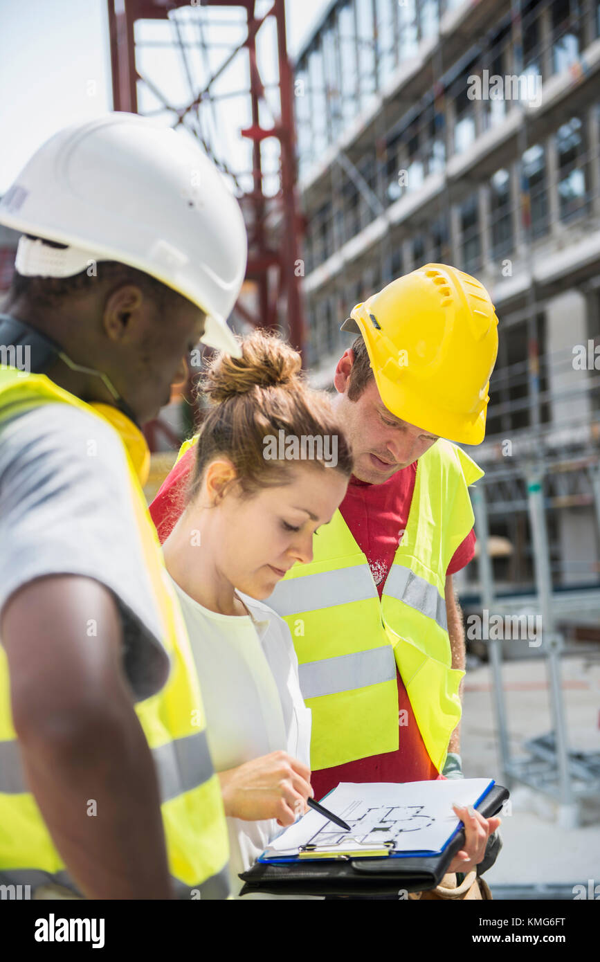 Architect reviewing blueprint with construction workers at building architect reviewing blueprint with construction workers at building site malvernweather Image collections