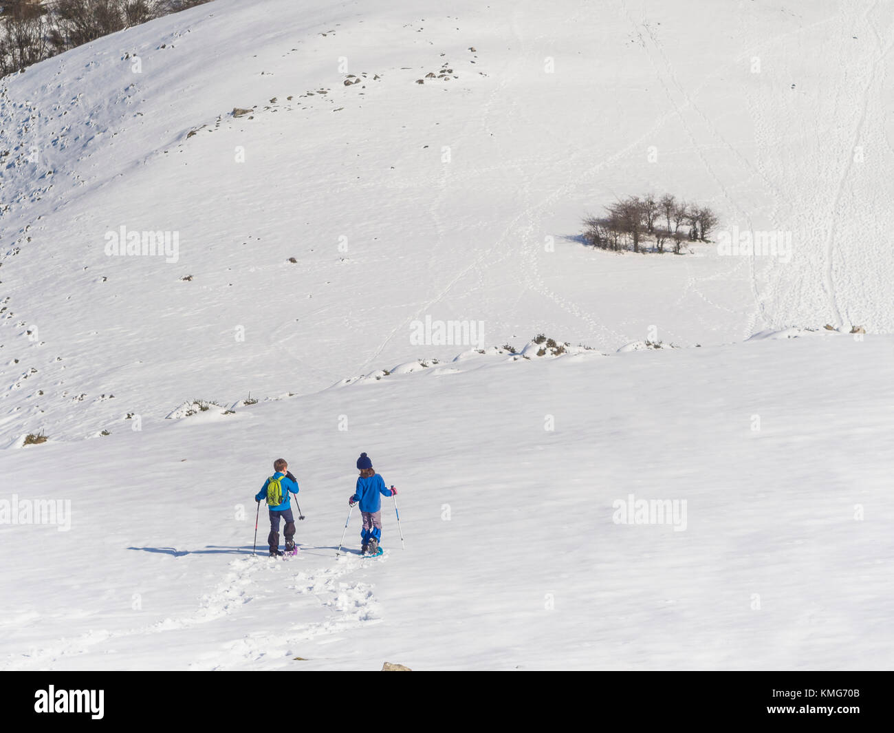 Boy and girl with snowshoe walking over snowfield at Mount Anboto - Stock Image