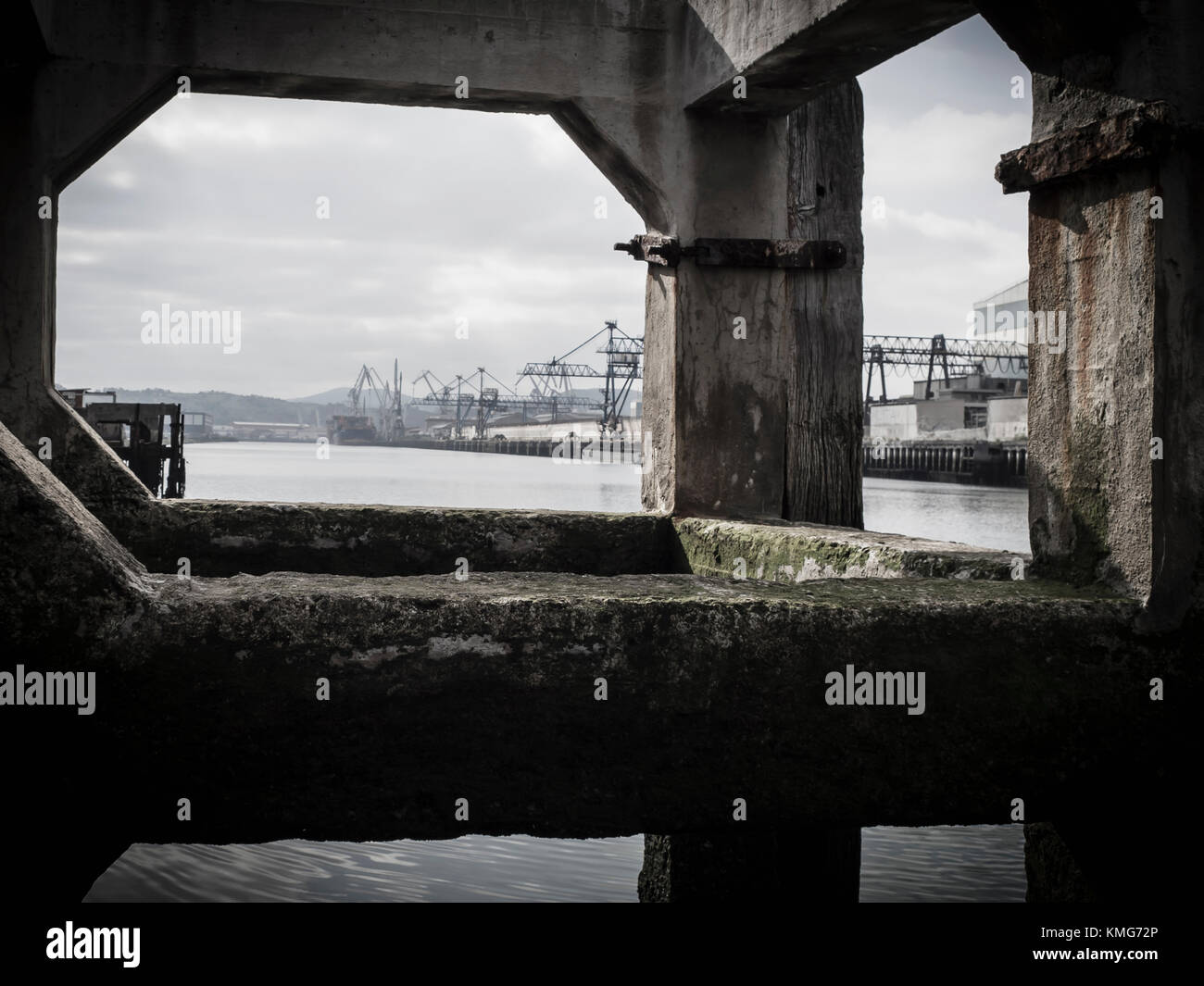 View of Bilbao river with construction crane on commercial dock - Stock Image