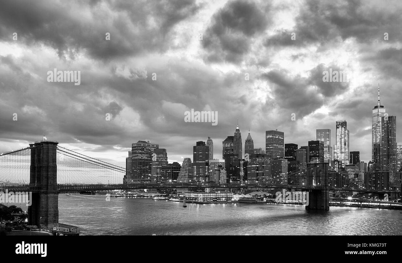 Black and white picture of Manhattan and Brooklyn Bridge with dramatic cloudscape at dusk, New York, USA. - Stock Image