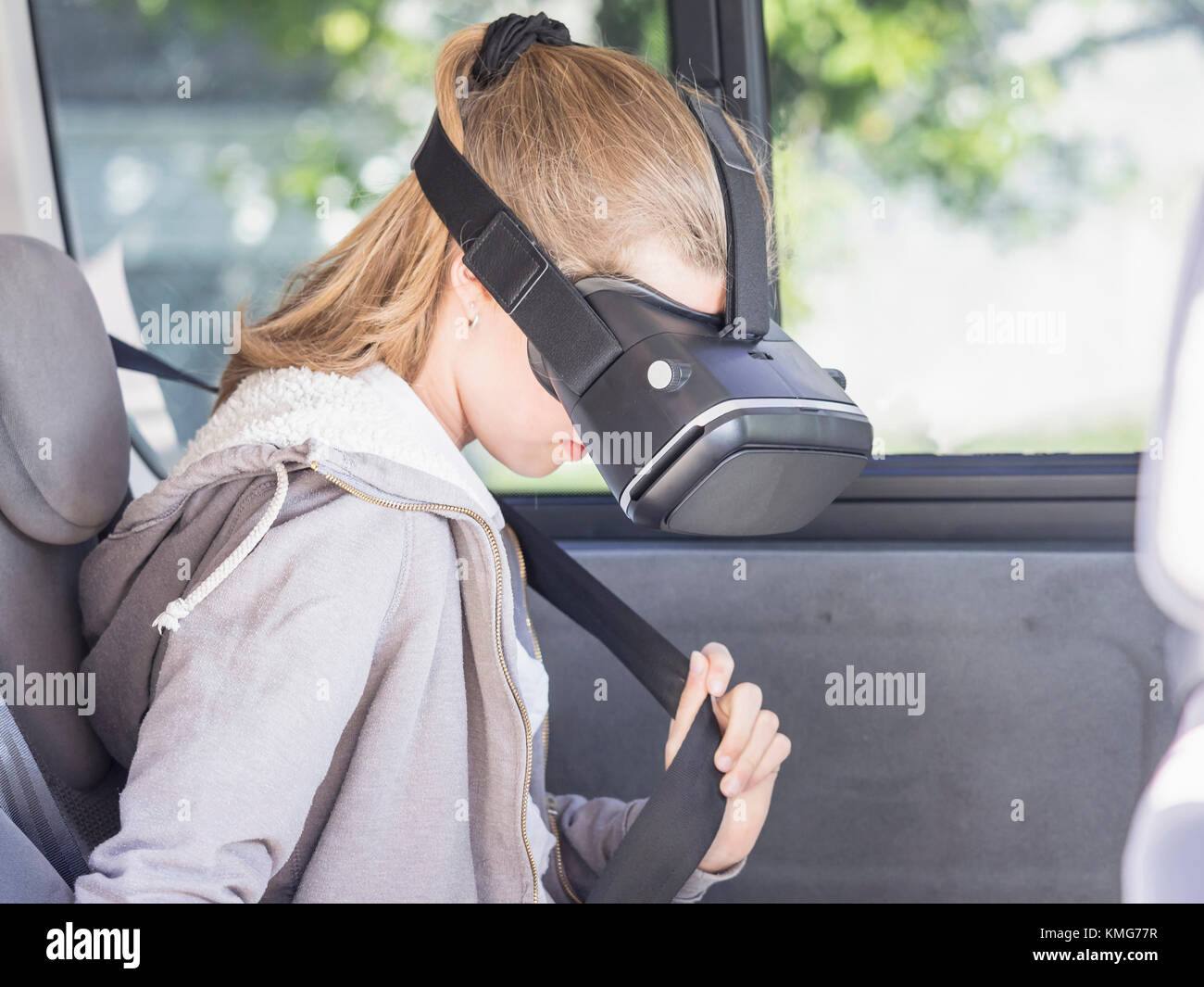 Girl using virtual reality headset while adjusting car seatbelt - Stock Image