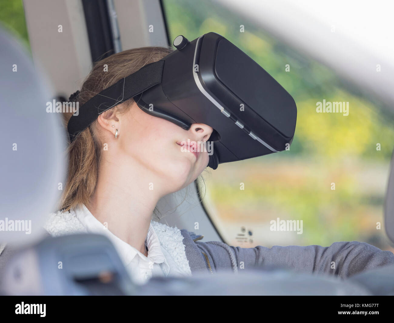 Girl using virtual reality headset in car - Stock Image