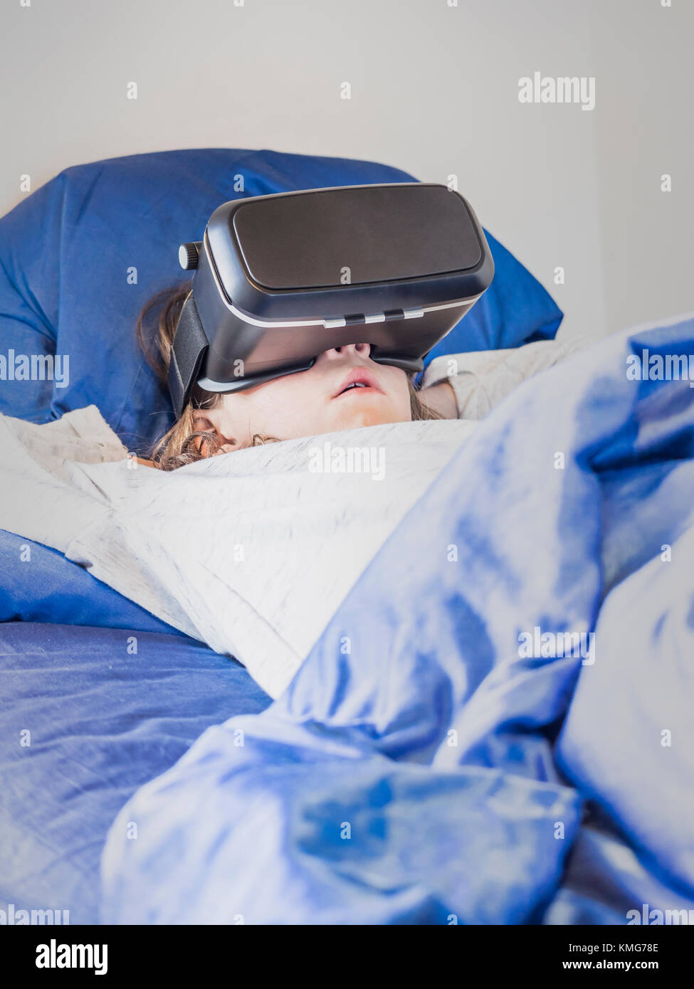 Girl with virtual reality glasses relaxing on bed - Stock Image