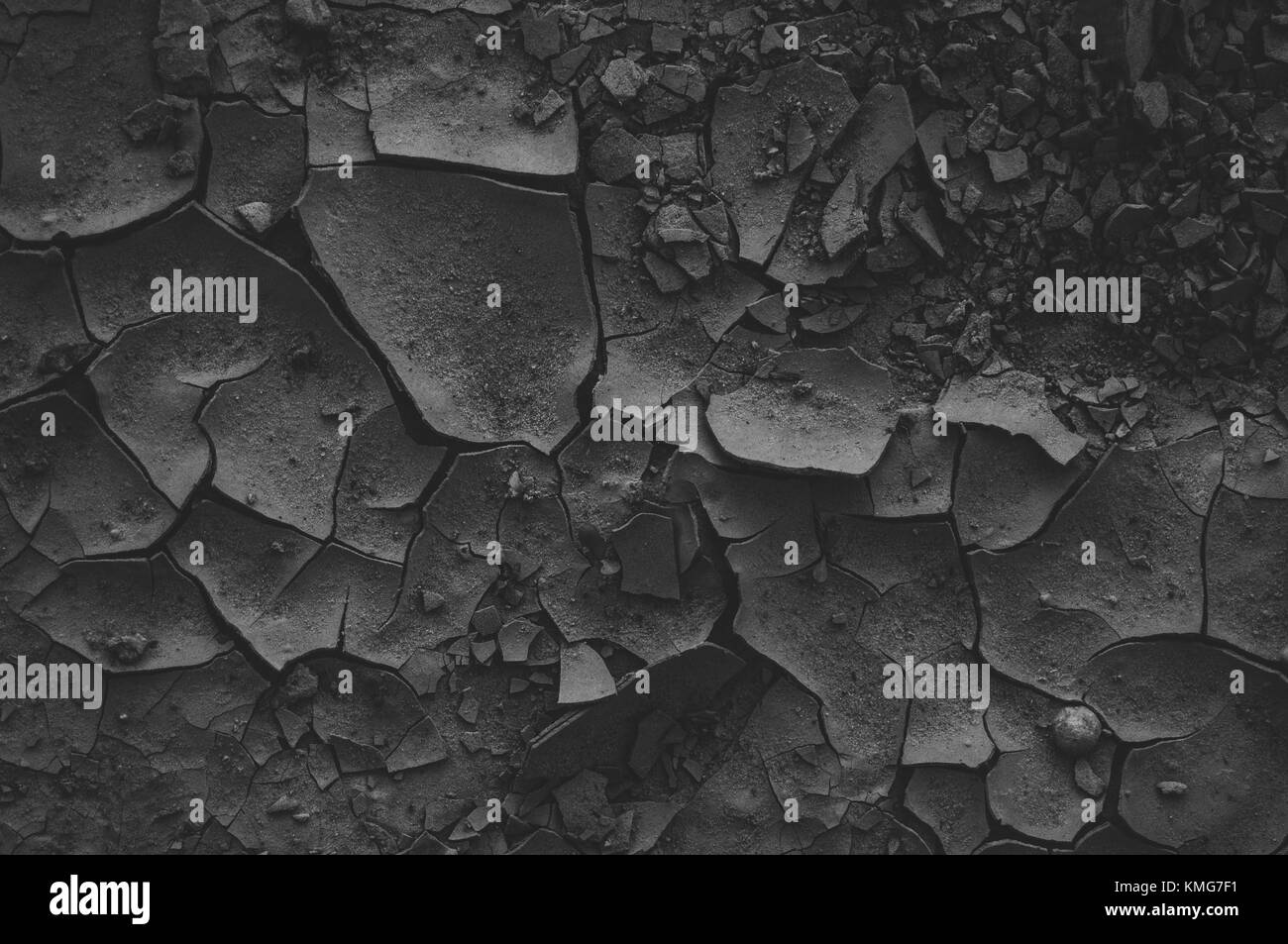 Dramatic cracked mud. Black and deep background. - Stock Image