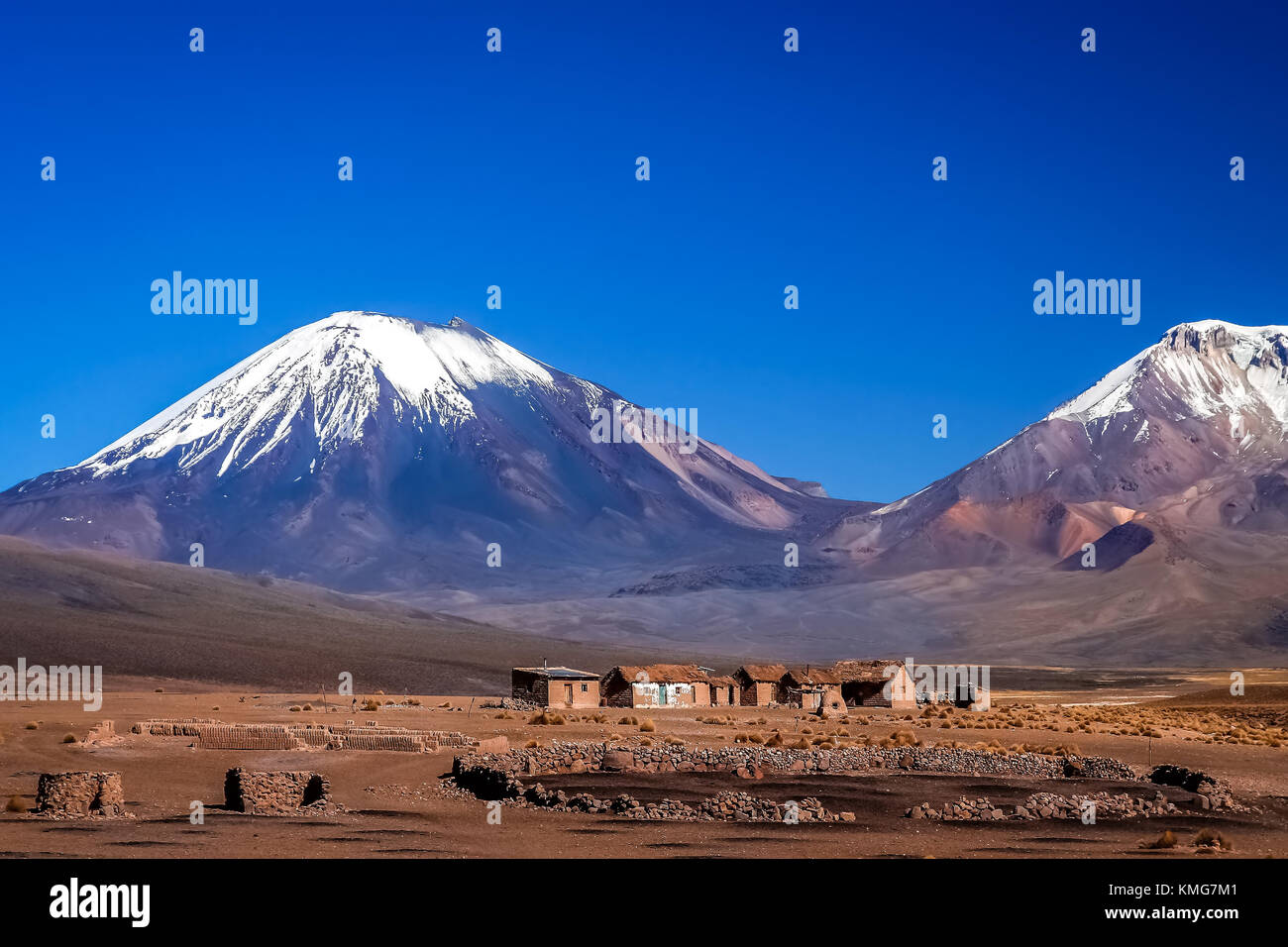 Abandoned homes and houses at the foot of two enormous volcanos, Nevado Sajama and Parinacota in the National Park, - Stock Image