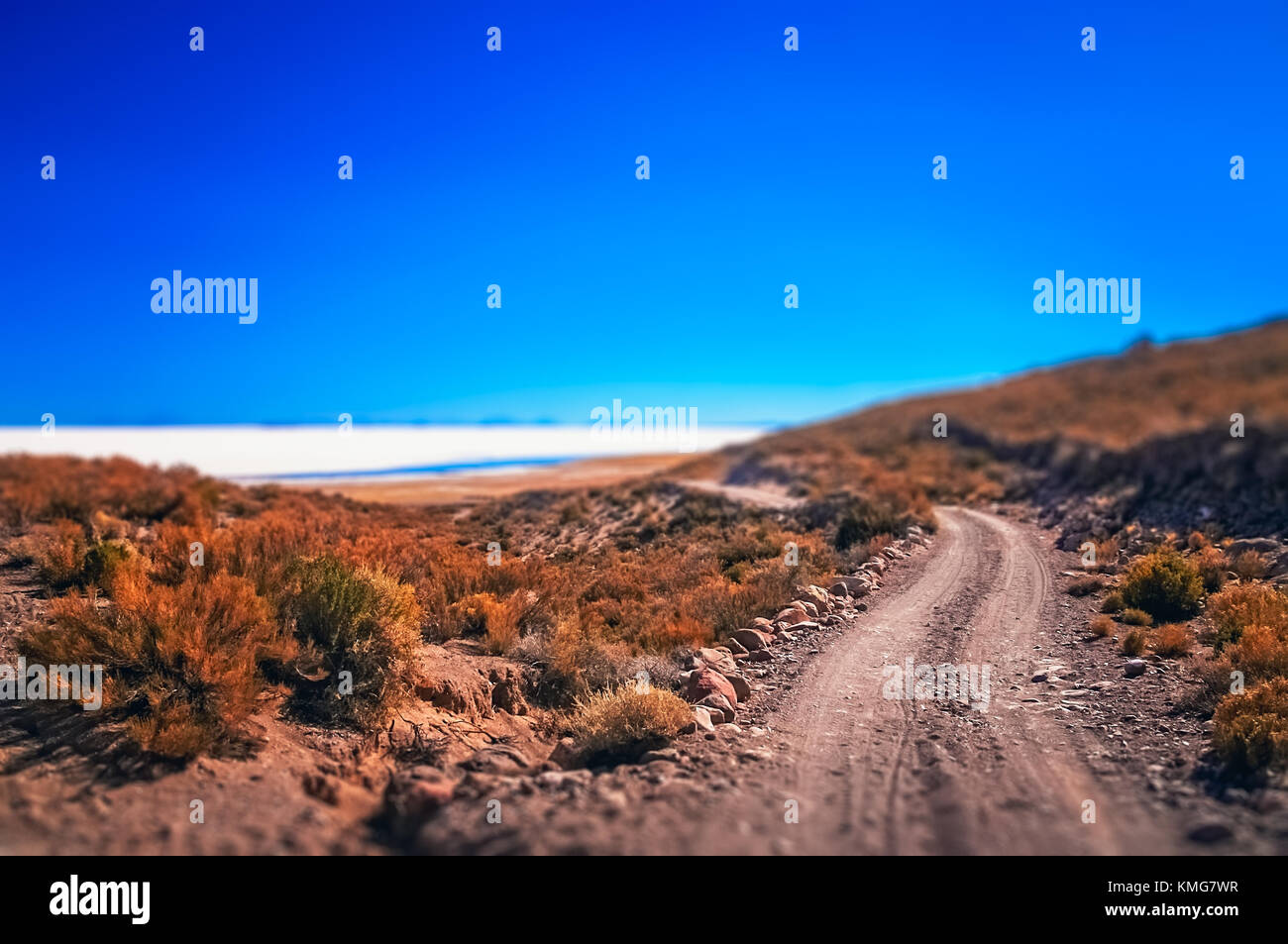 Remote road leading to the biggest of salt lakes, Salar de Uyuni in Bolivia - Stock Image