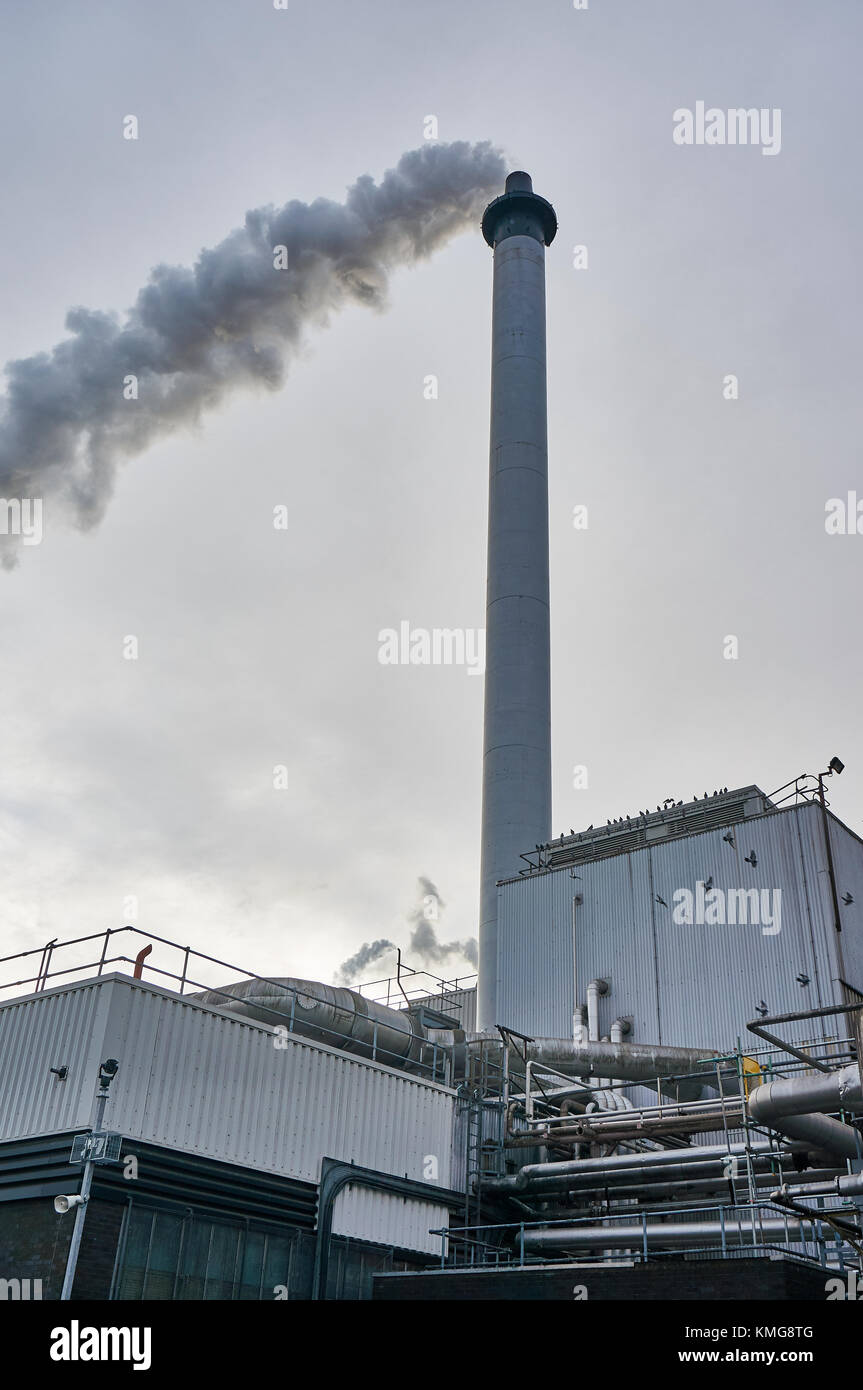 Glasgow, Scotland - 1 December 2017 : A chimney from Strathclyde whiskey distillery releasing steam and smoke into - Stock Image