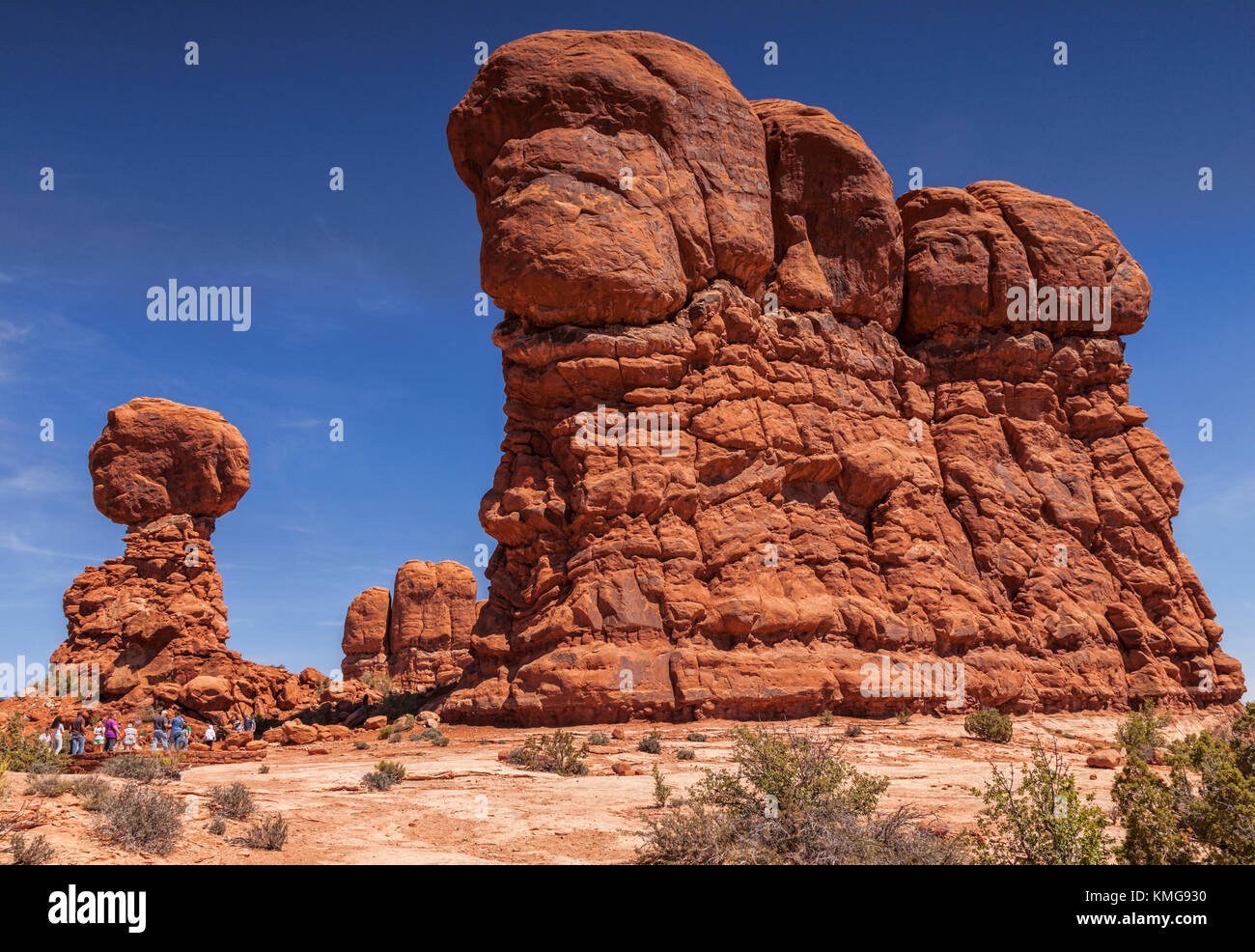 A group of tourists show the massive scale of the eroded sandstone formations in Arches National Park. Balanced - Stock Image