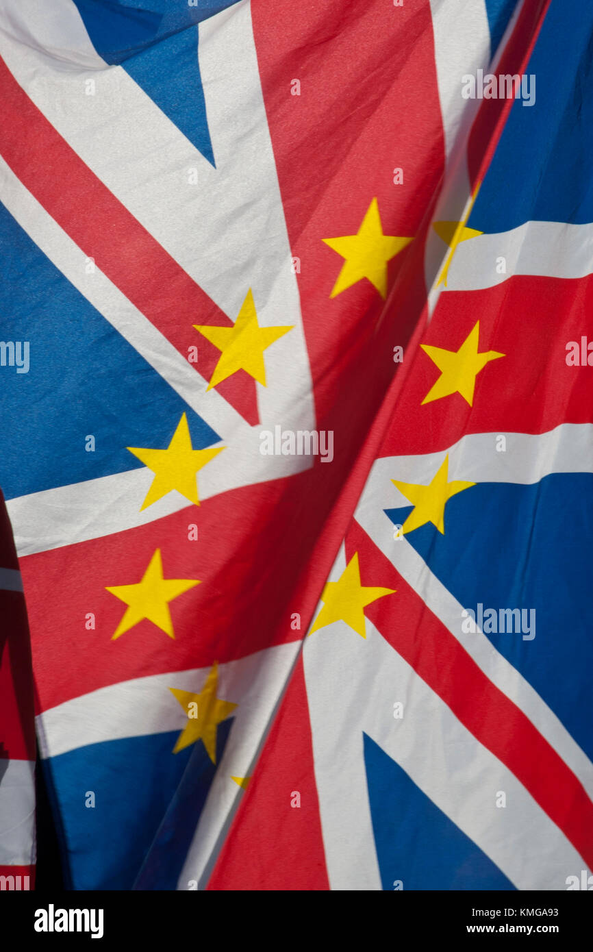 Close up of UK Union Jack with gold stars of European flag superimposed. Flag is 'flapping' with big fold - Stock Image
