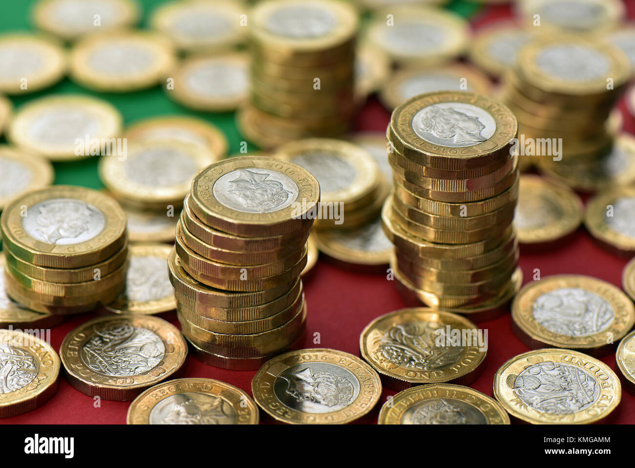 pound coins in large quantities on a red and green Christmassy themed background. Christmas spending and coins in Stock Photo