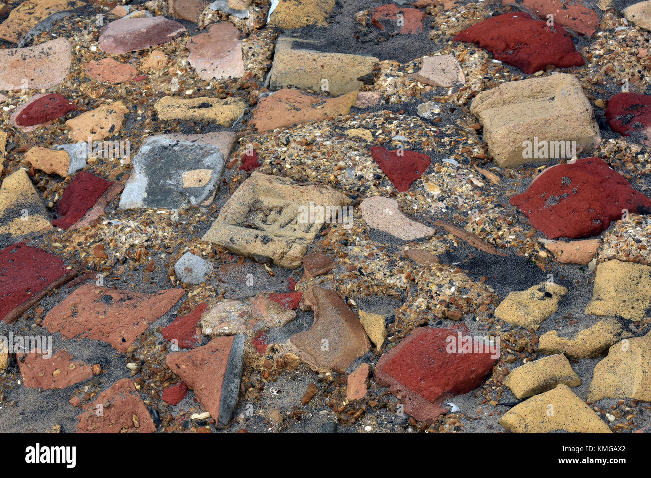 a selection of different pieces of broken building bricks, stones and materials set in some concrete in a random - Stock Image