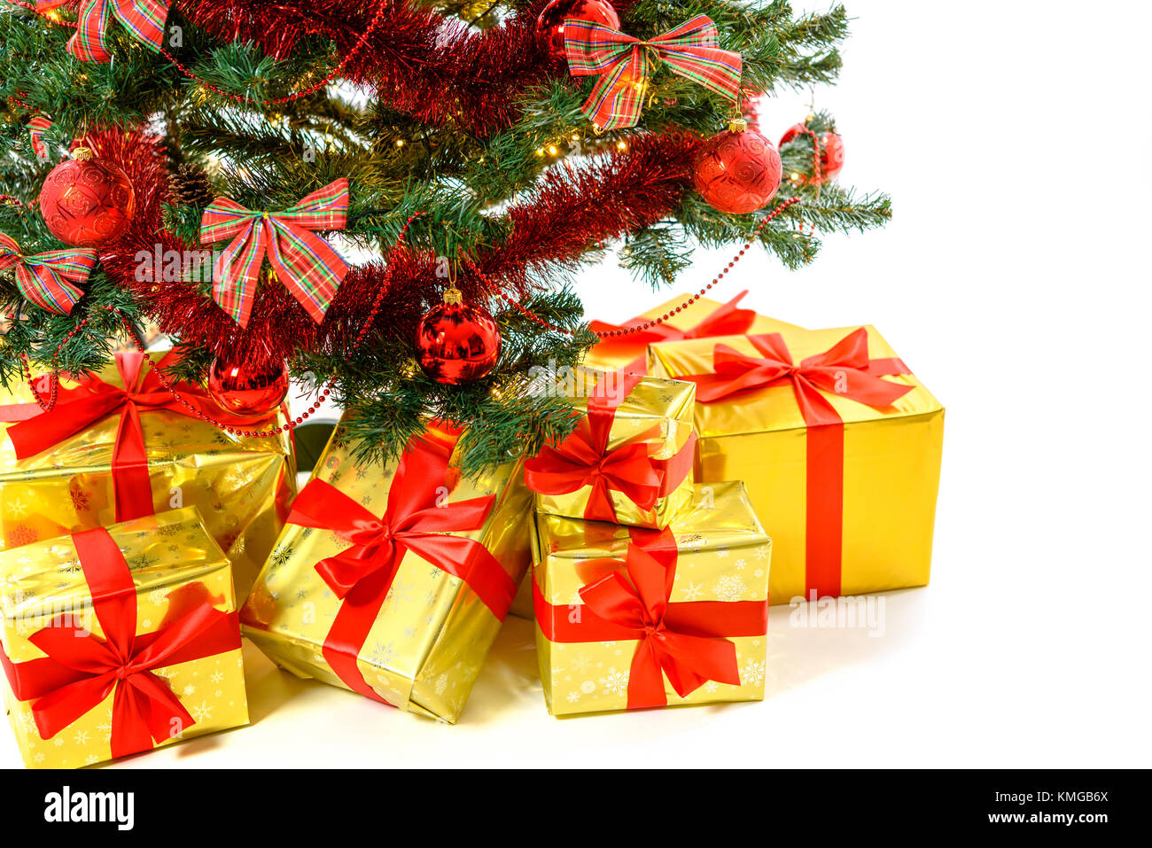luxury golden colored gifts with red ribbon under a beautiful christmas tree with red balls bows and lights isolated on white background in close up