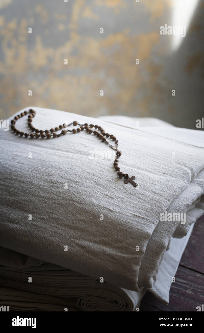 Rosary beads and cross on linen. Stock Photo