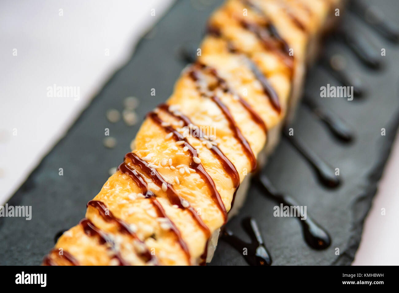 Freshly cooked uncut sushi roll on black board - Stock Image