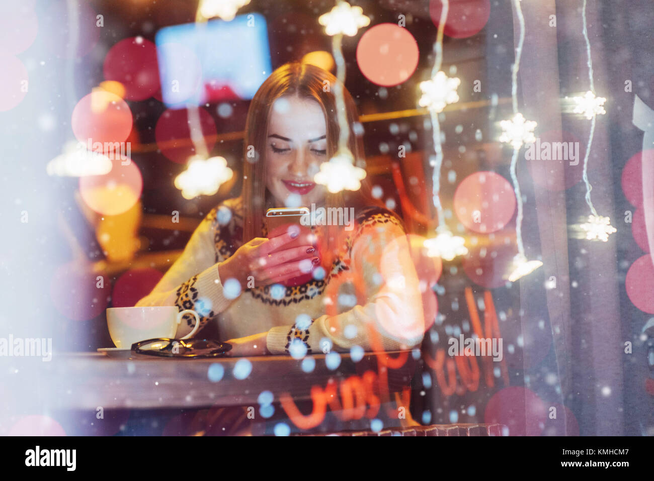 Young beautiful woman sitting in cafe, drinking coffee. Magic snowfall effect. Christmas, new year, Valentines day, - Stock Image
