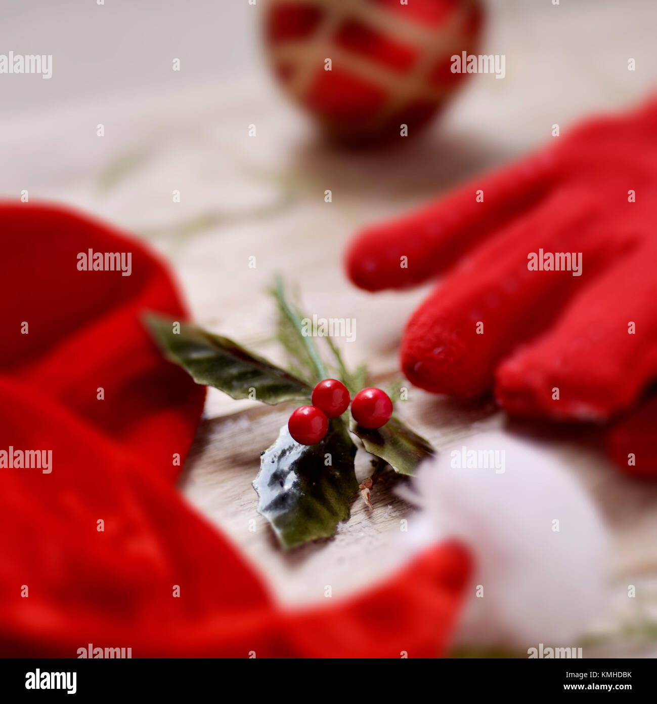 closeup of a santa hat, a pair of cozy red gloves, a red chrismtas ball and a twig of holly on a white rustic  wooden - Stock Image