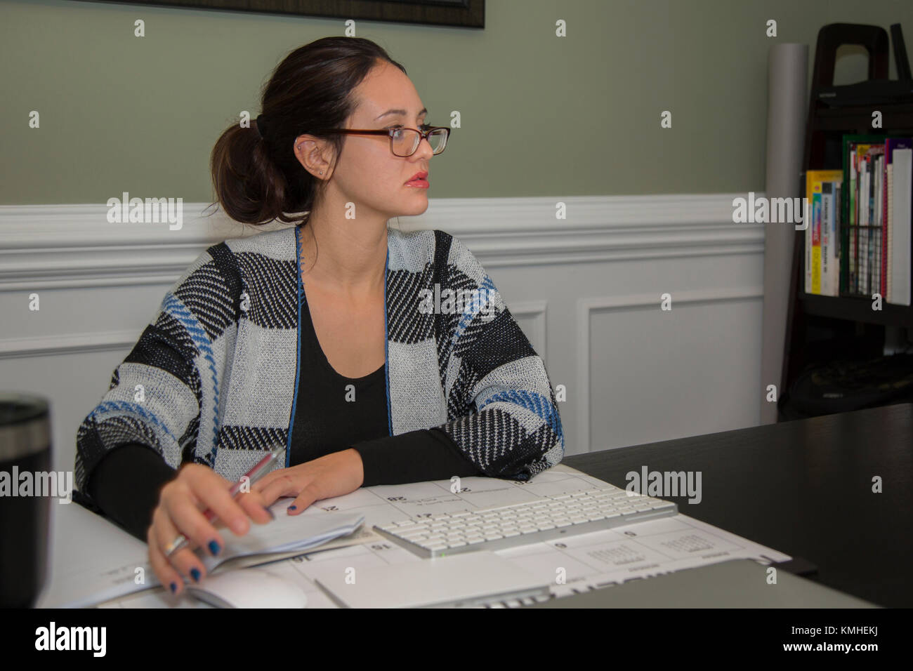 Beautiful 20-25 year old white female studying in her home office. - Stock Image