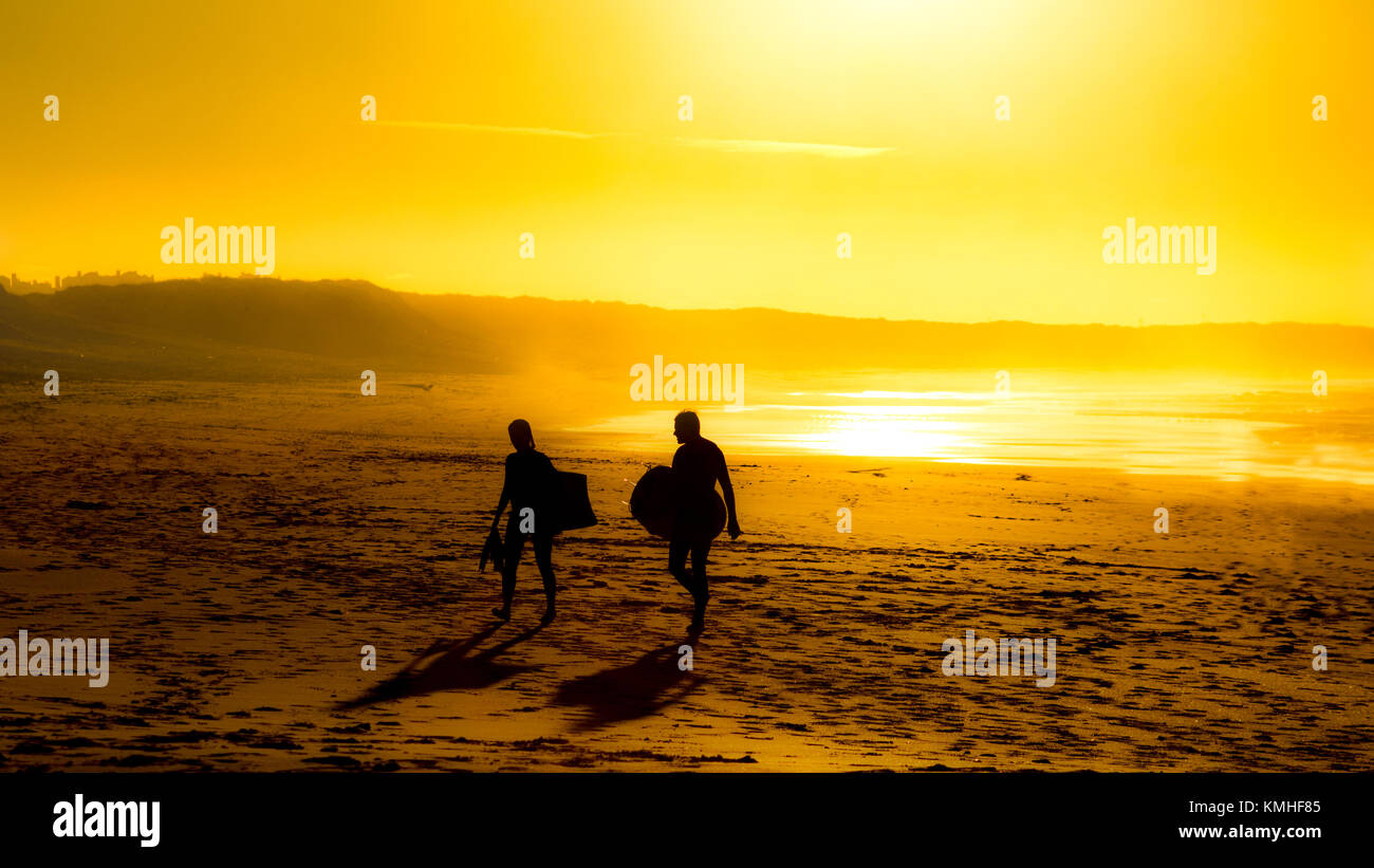 Surfers leaving Peniche beach at sunset - Stock Image