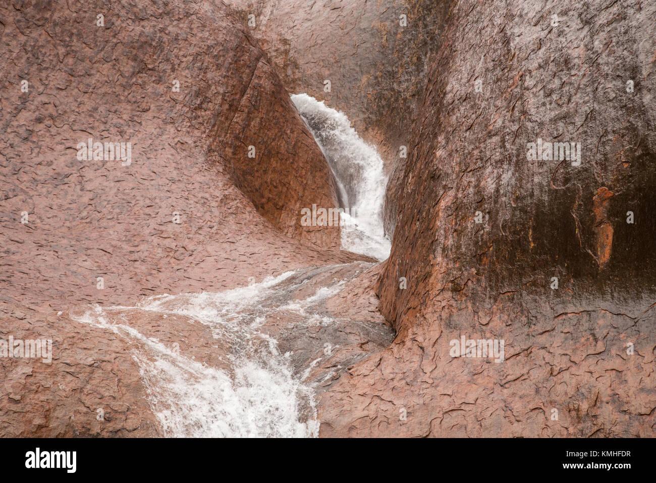 Ayers Rock in the rain - waterfalls on Uluru during a rare rainstorm in Uluru Kata Tjuta National Park, Northern - Stock Image