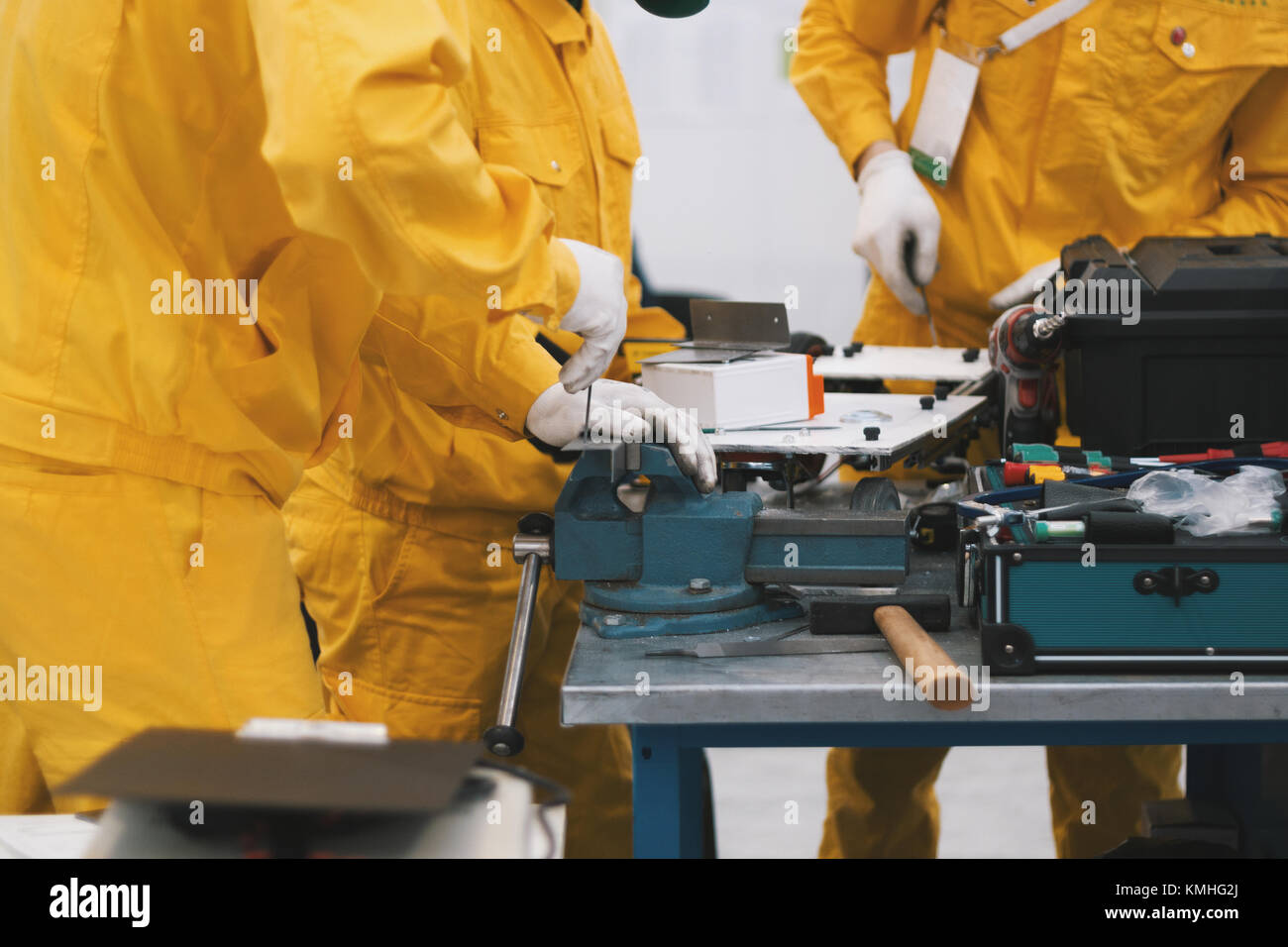 Engineers and workers in yellow overalls working in metal workshop - Stock Image