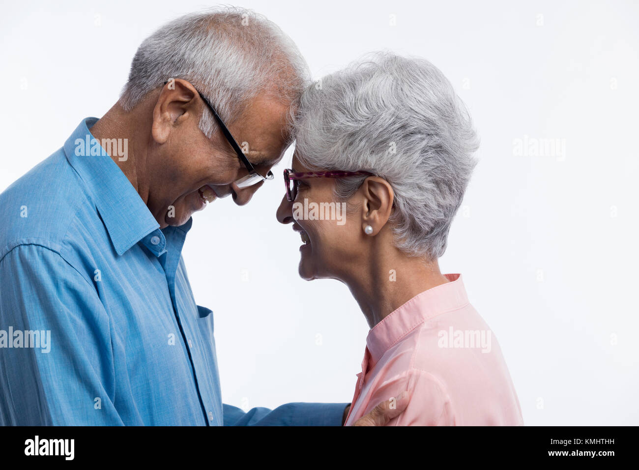 Senior couple looking at each other touching heads - Stock Image