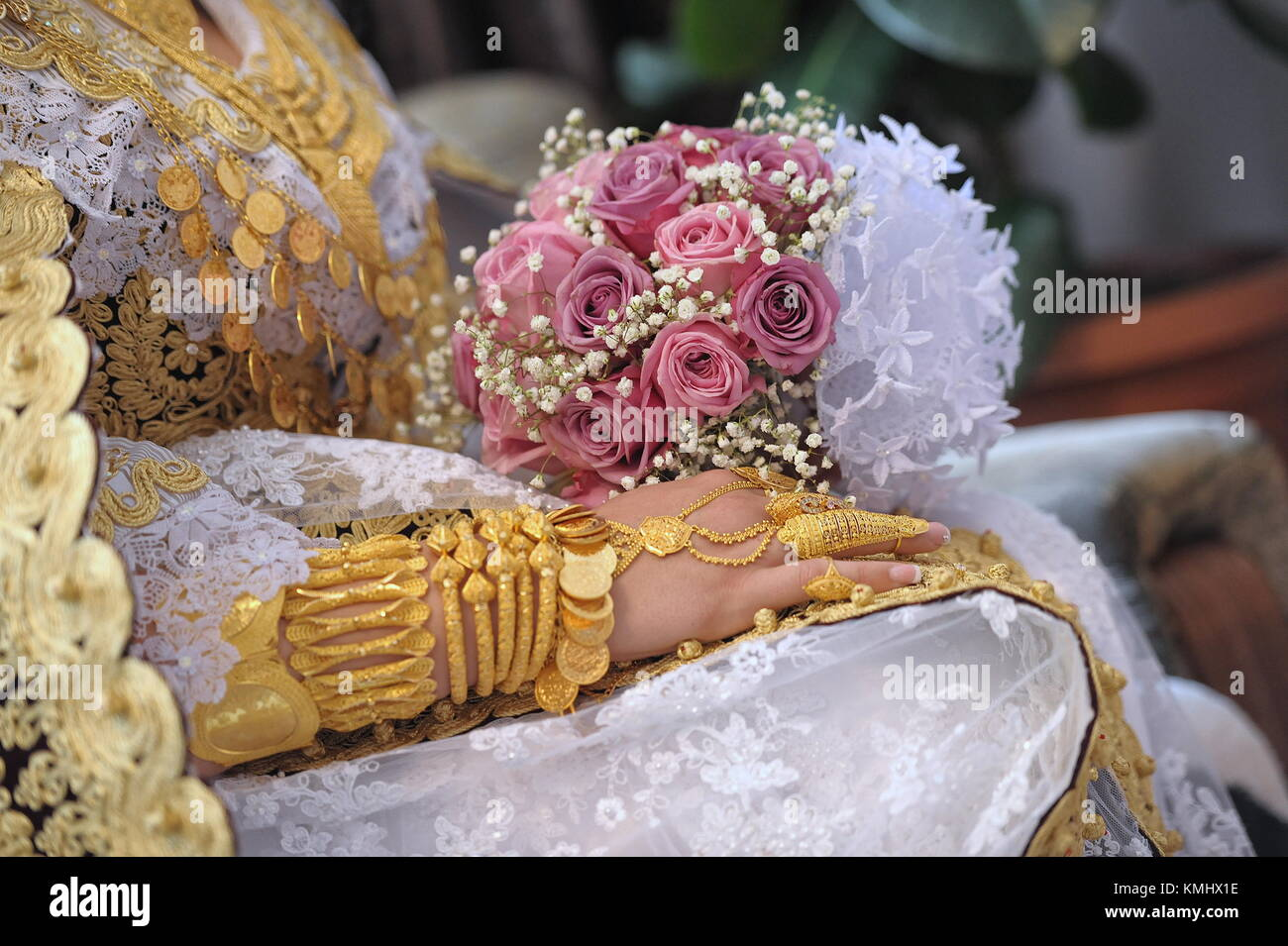 Gold jewelry and roses on the hands of a Muslim bride - Stock Image