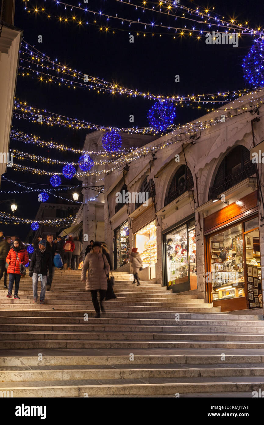 Illuminated Christmas lights on Rialto Bridge, Venice, Italy at night with brightly lit shops and people walking - Stock Image