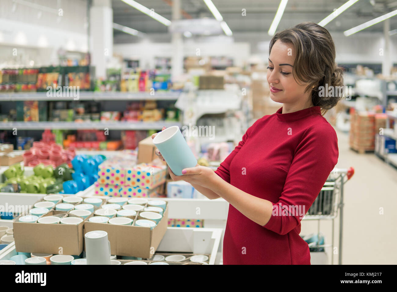 housewife customer choosing cup or mug in big supermarket mall - Stock Image