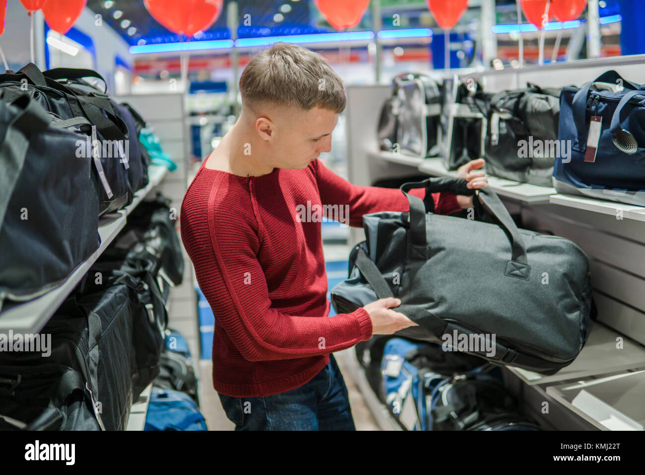 hipster man purchasing stylish backpack in supermarket store - Stock Image