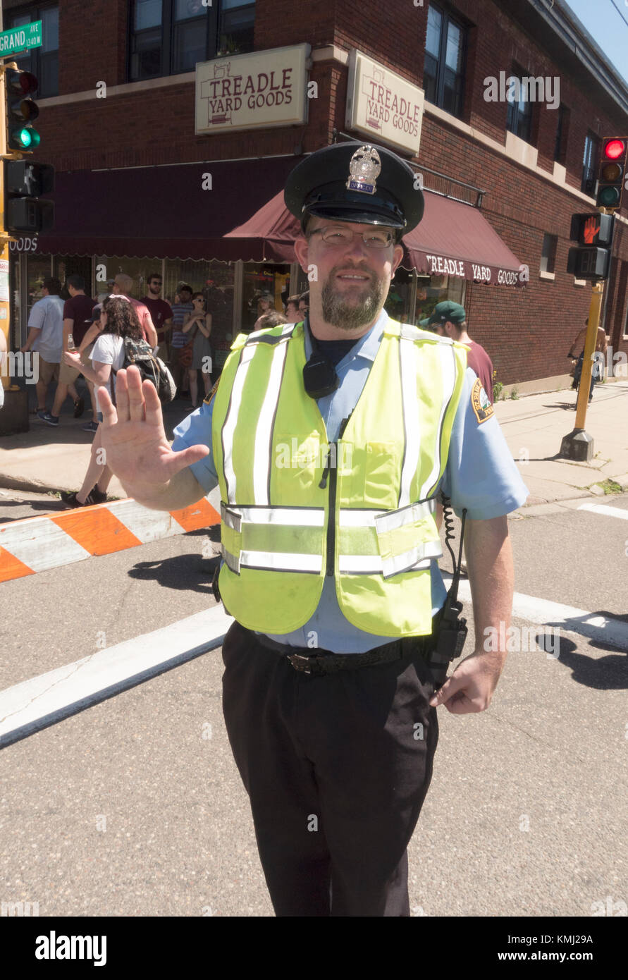 Policeman wearing a florescent safety vest directing traffic at Grand Old Day festivities. St Paul Minnesota MN - Stock Image