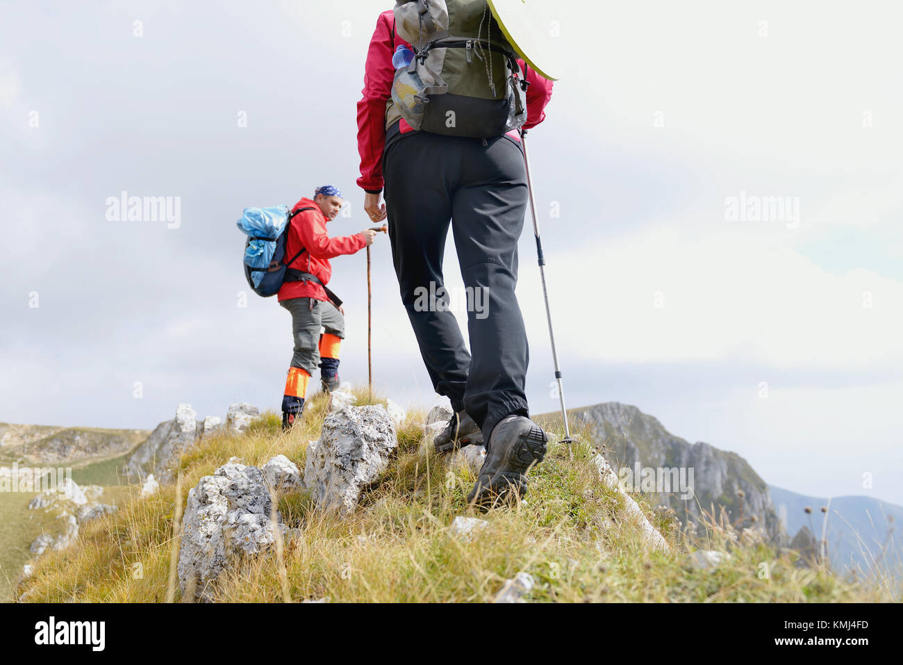 Close-up of legs of young hikers walking on the country path. Young couple trail waking. Focus on hiking shoes - Stock Image