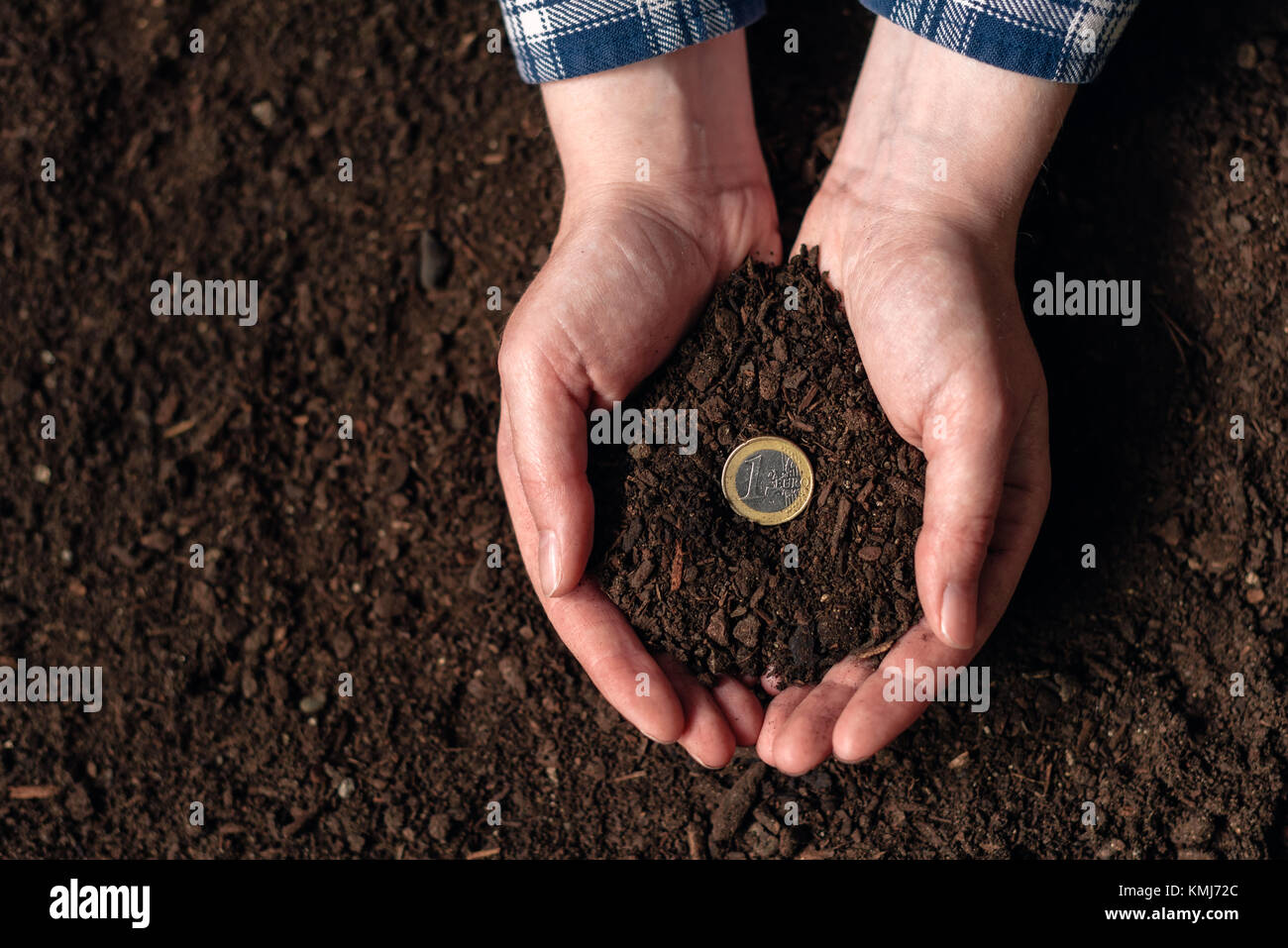 Making money from agricultural activity and earning extra income, female farmer handful of soil with euro coin - Stock Image