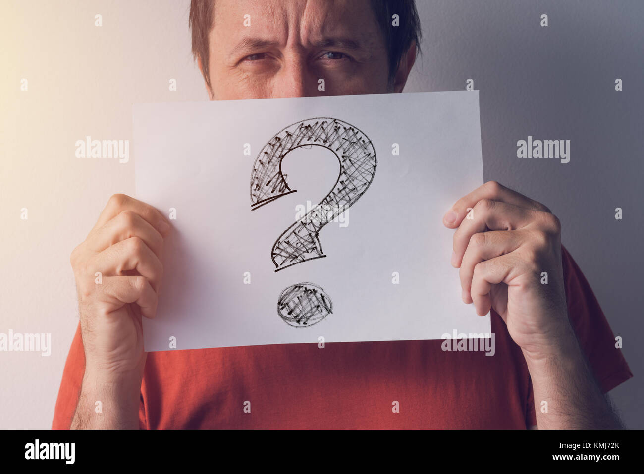 Question mark, looking for answers. Man holding paper with scribbled interrogation point, query, or eroteme punctuation - Stock Image