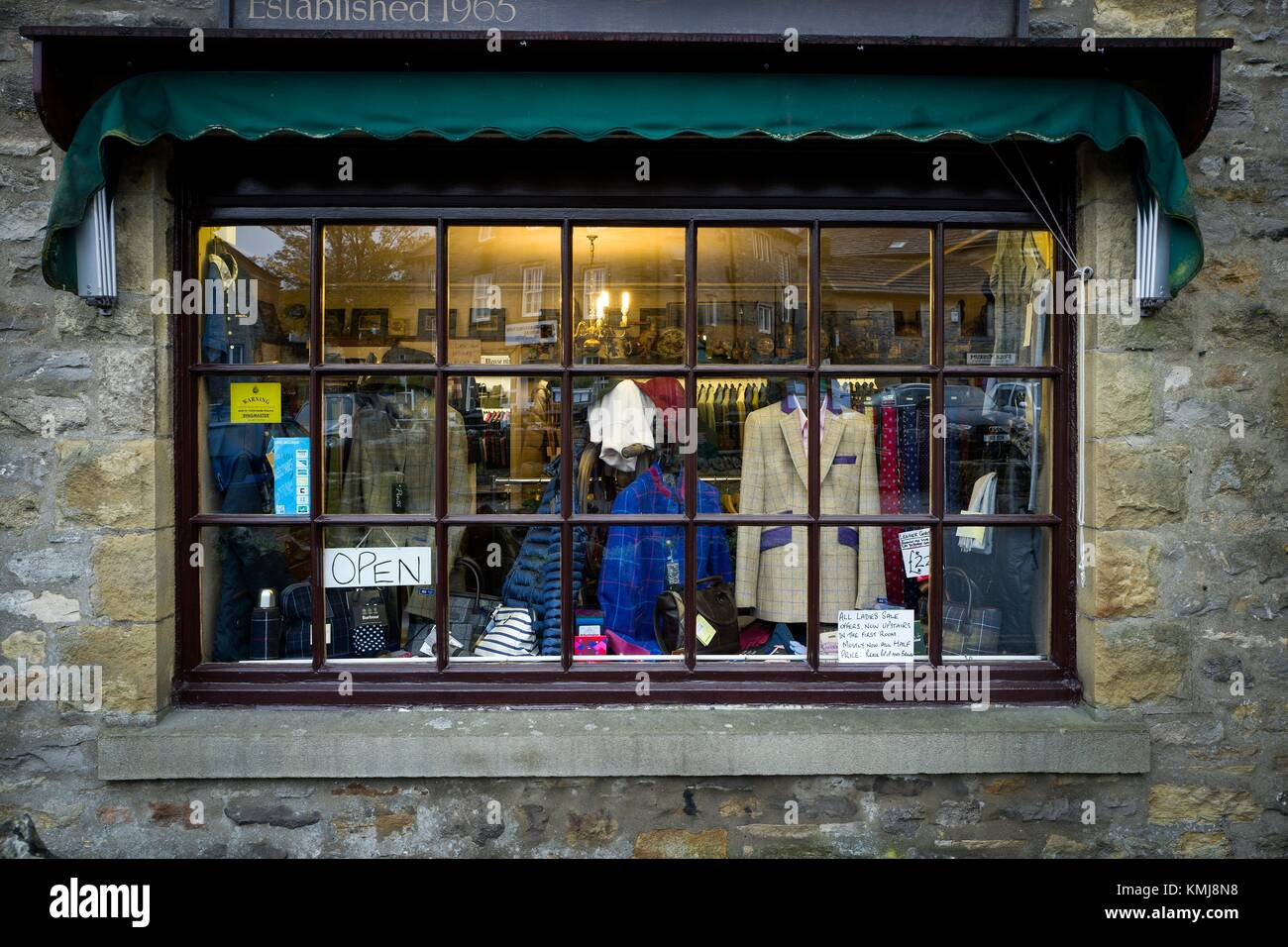 Shop window of a traditional English clothing store with the 'OPEN' sign. Grassington, Yorkshire Dales, - Stock Image