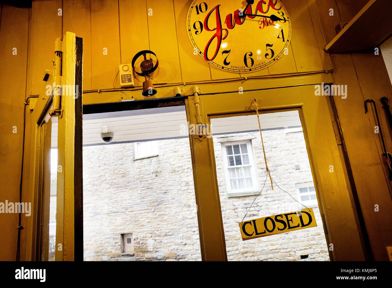 """Open shop door, wall clock and """"closed"""" sign. Hawes, Richmondshire, Yorkshire Dales, North Yorkshire, England, UK Stock Photo"""