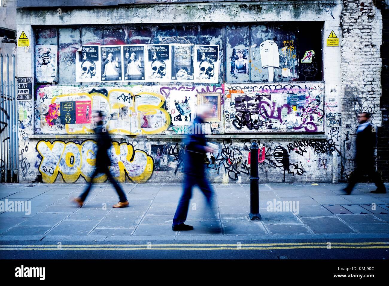 Tres personas irreconocibles andando por la acera de una calle y en la pared de fondo pintada con graffitis. Brick Stock Photo