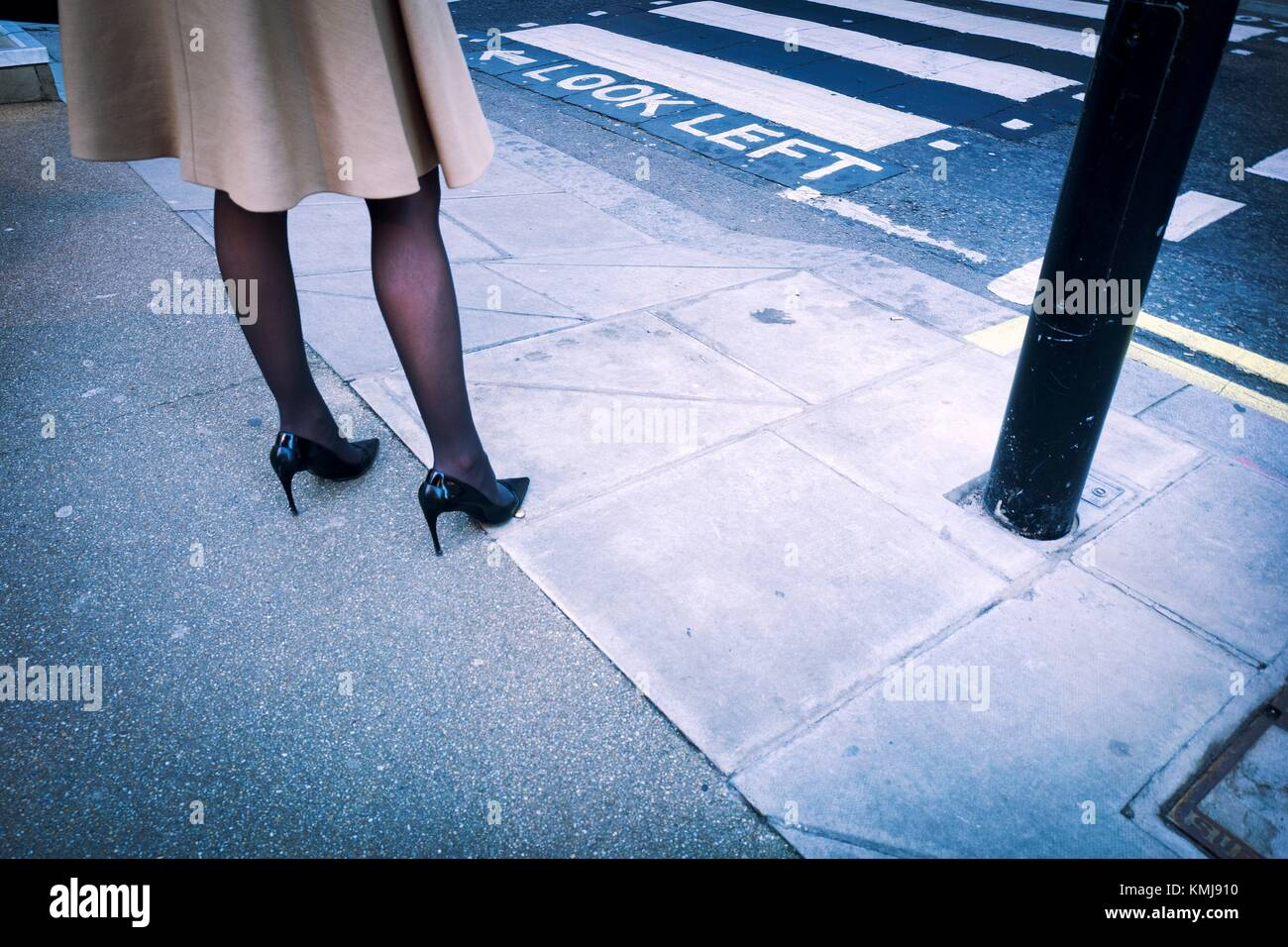 Close-up of the legs of a woman dressed in fashion with a coat, black stockings and high heels in the street beside - Stock Image
